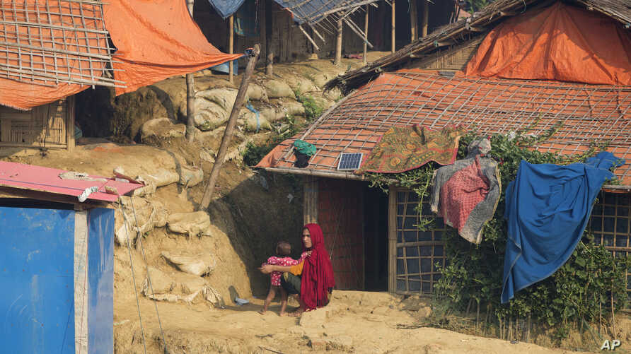 A Rohingya Muslim refugee sunbathes along with her child outside their shelter at Balukhali refugee camp near Cox's Bazar, in Bangladesh, Saturday, Nov. 17, 2018.