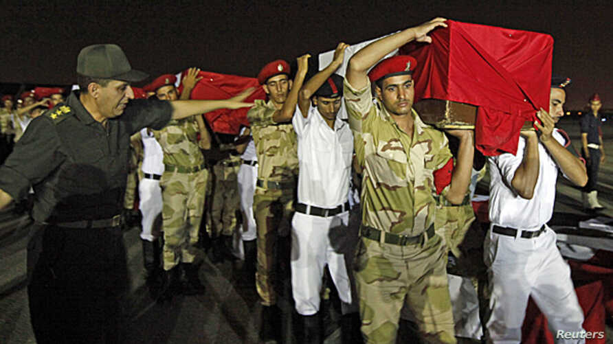 The caskets of 25 policemen killed early Monday morning near the north Sinai town of Rafah are carried after arriving at Almaza military airport in Cairo August 19, 2013.