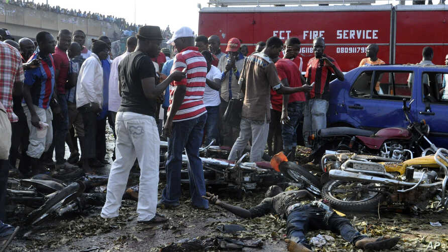 People gather at the site of a blast at the Nyanya Motor Park, about 16 kilometers (10 miles) from the center of Abuja, Nigeria, April 14, 2014.