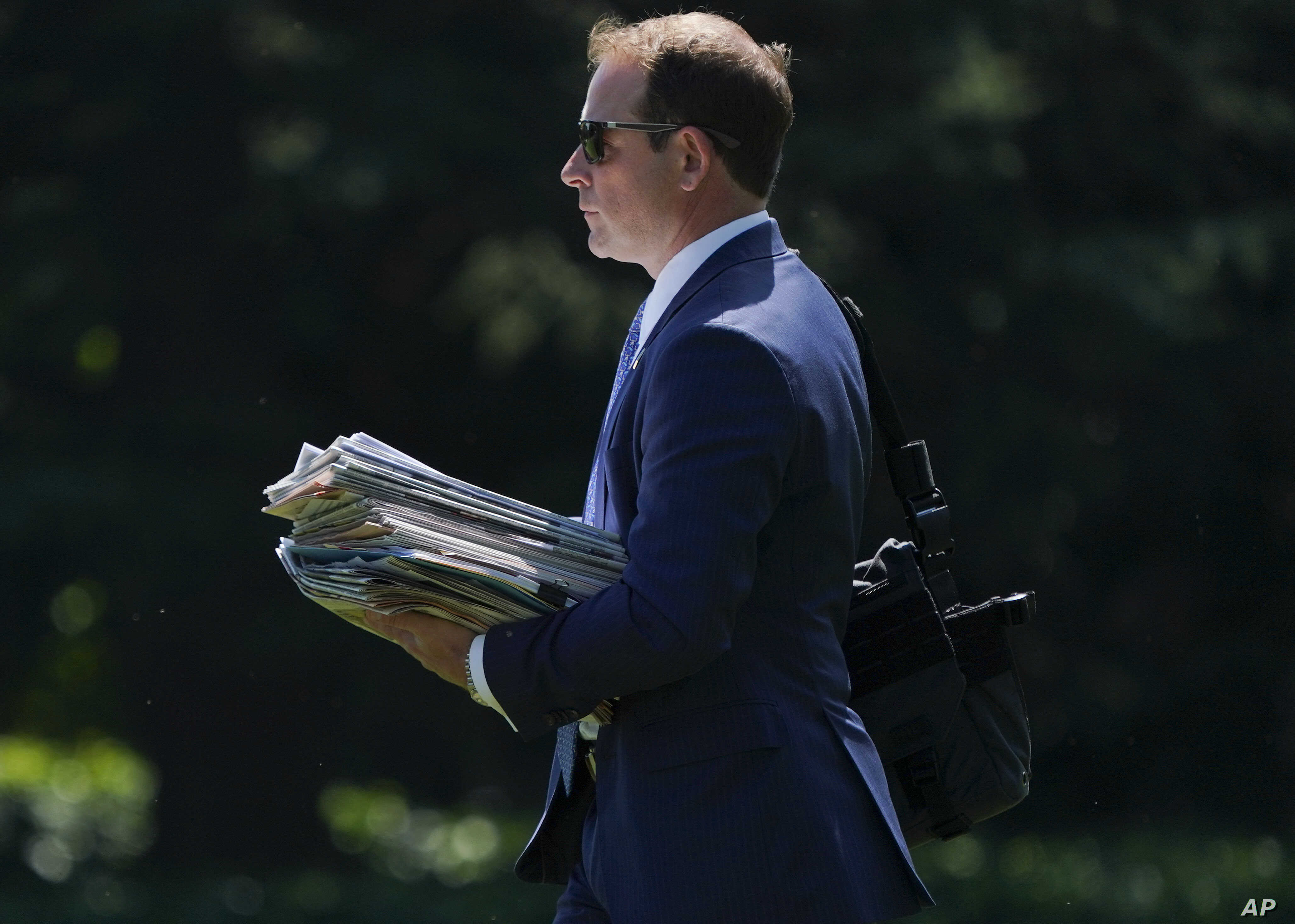 FILE - Jordan Karem, right, Deputy Assistant to the President and Director of Oval Office Operations, carries newspapers as he walks across the South Lawn of the White House in Washington, Aug. 24, 2018.