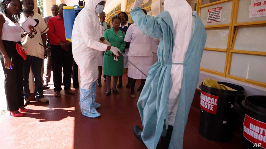A nurse is sprayed during a tour of one of the Ebola Centers in Harare, Zimbabwe, Sept. 23, 2014.