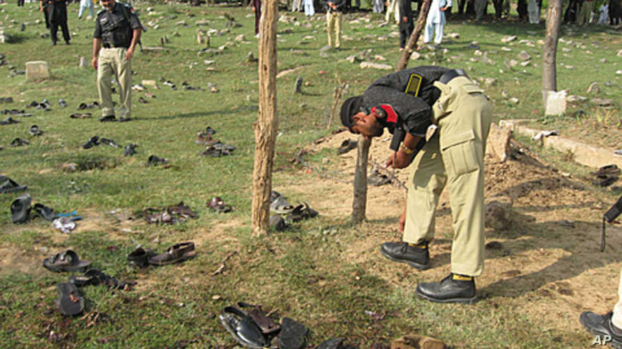 Pakistani police officers collect evidence at the spot of a suicide bombing in Shina Samar Bagh in Lower Dir, Pakistan, September 15, 2011.