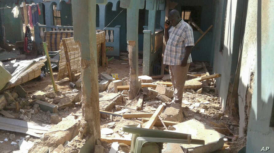 A man stands amid the debris at the scene of an attack in the town of Mandera, Kenya, near the border with Somalia, Oct. 25, 2016.