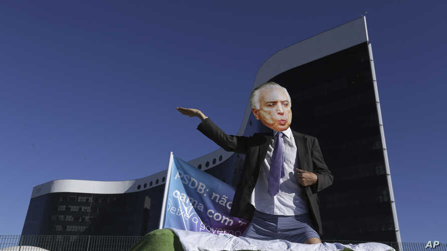 A demonstrator wearing a mask depicting Brazil's President Michel Temer performs during a protest outside the Superior Electoral Court in Brasilia, Brazil, June 7, 2017.