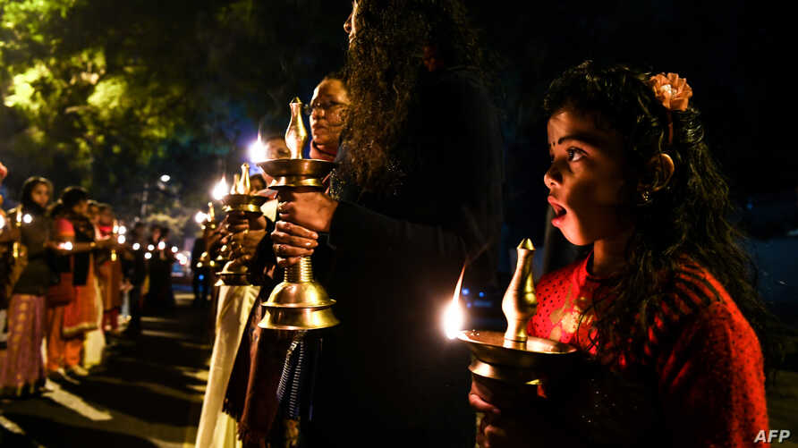 Indian Hindu activists participate in a candlelight vigil outside Kerala State house, as they protest against Kerala government supporting women devotees entering in the Sabarimala Ayyapa temple in the southern state of Kerala, in New Delhi, Dec. 26,