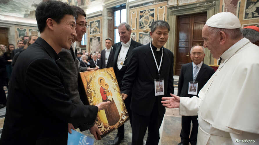 """Pope Francis receives a gift during a special audience with participants in a conference titled """"Perspectives for a World Free from Nuclear Weapons and for Integral Disarmament"""" at the Vatican, Nov. 10, 2017."""
