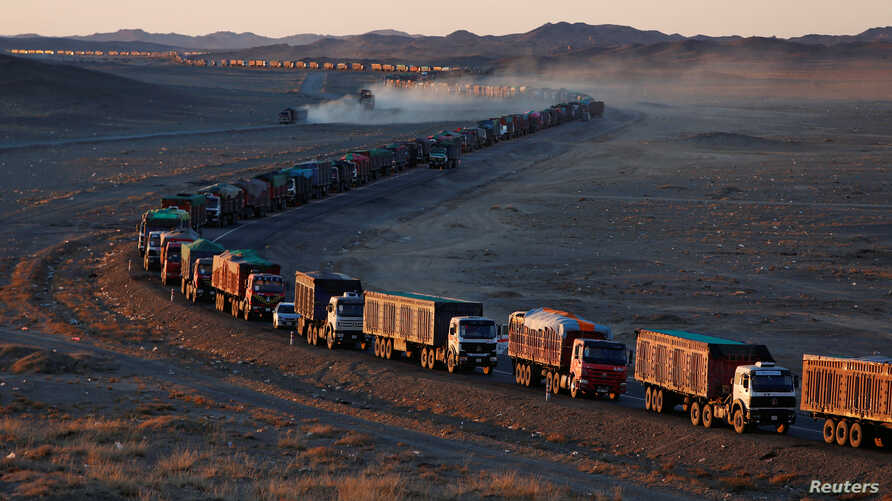 Thousands of heavy-duty trucks loaded with coal are lined up for up to 130 kilometers from the Mongolia-China border on a sole road in the Gobi desert, Mongolia, Oct. 29, 2017. The journey can take more than a week.