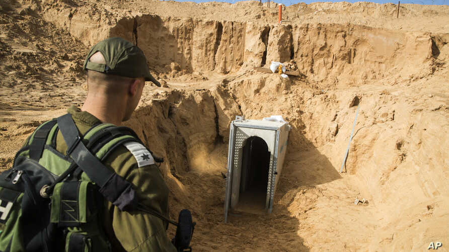 An Israeli soldier stands on the Israeli side of the border with Gaza, near the opening of a tunnel, that Israel says was dug by the Islamic Jihad militant group, leading from Gaza into Israel, near the southern Israeli kibbutz of Kissufim, Israel, J