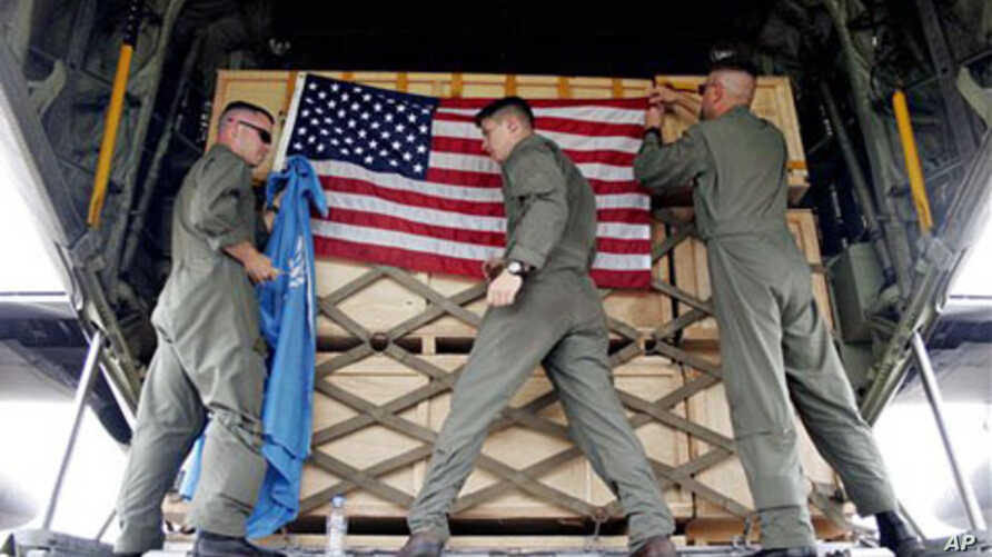 US soldiers from Marine Aircraft Group 36 adjust flags on a cargo of  aid after loading it onto a cargo plane, (File)