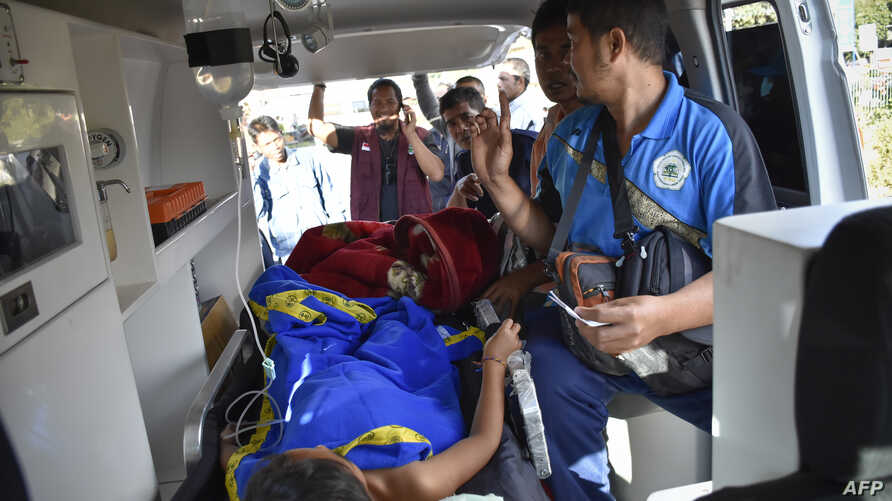 Members of an Indonesian medical team transport an earthquake survivor in an ambulance in Lombok on July 29, 2018.