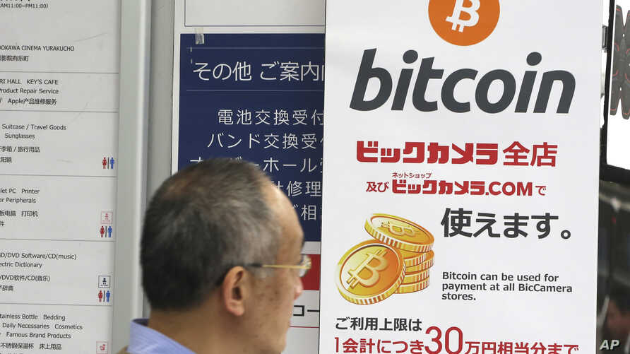 FILE - A man walks past a poster of bitcoin displayed at a retail store in Tokyo, Jan. 19, 2018.