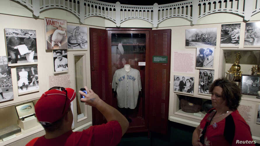 FILE - Visitors look at the jersey of baseball great Babe Ruth displayed in a Yankee Stadium locker at the National Baseball Hall of Fame in Cooperstown, New York.