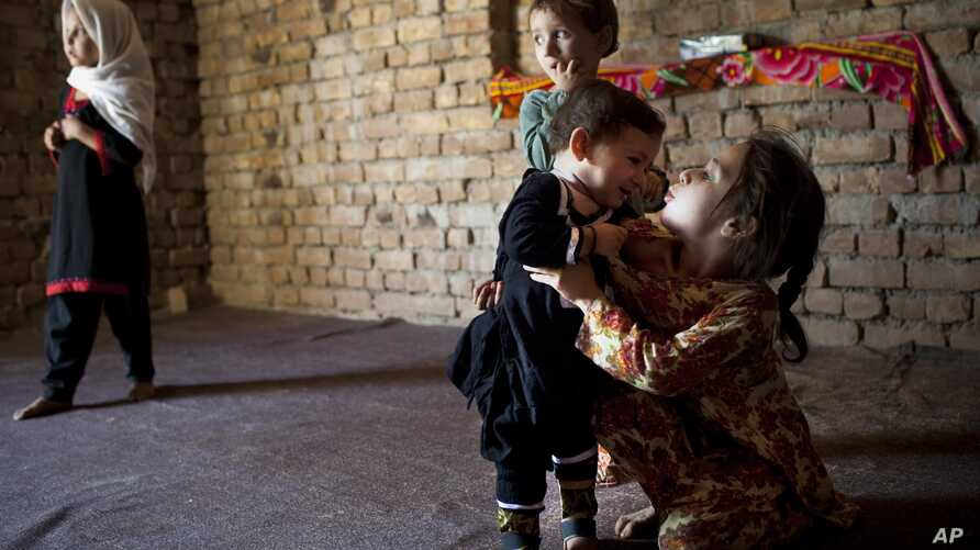 Fariha, a 13-month-old polio victim whose legs are bound in small plastic braces, is attended by her older sister Sana, Aziz Khan Ghari, Pakistan, May 30, 2012.