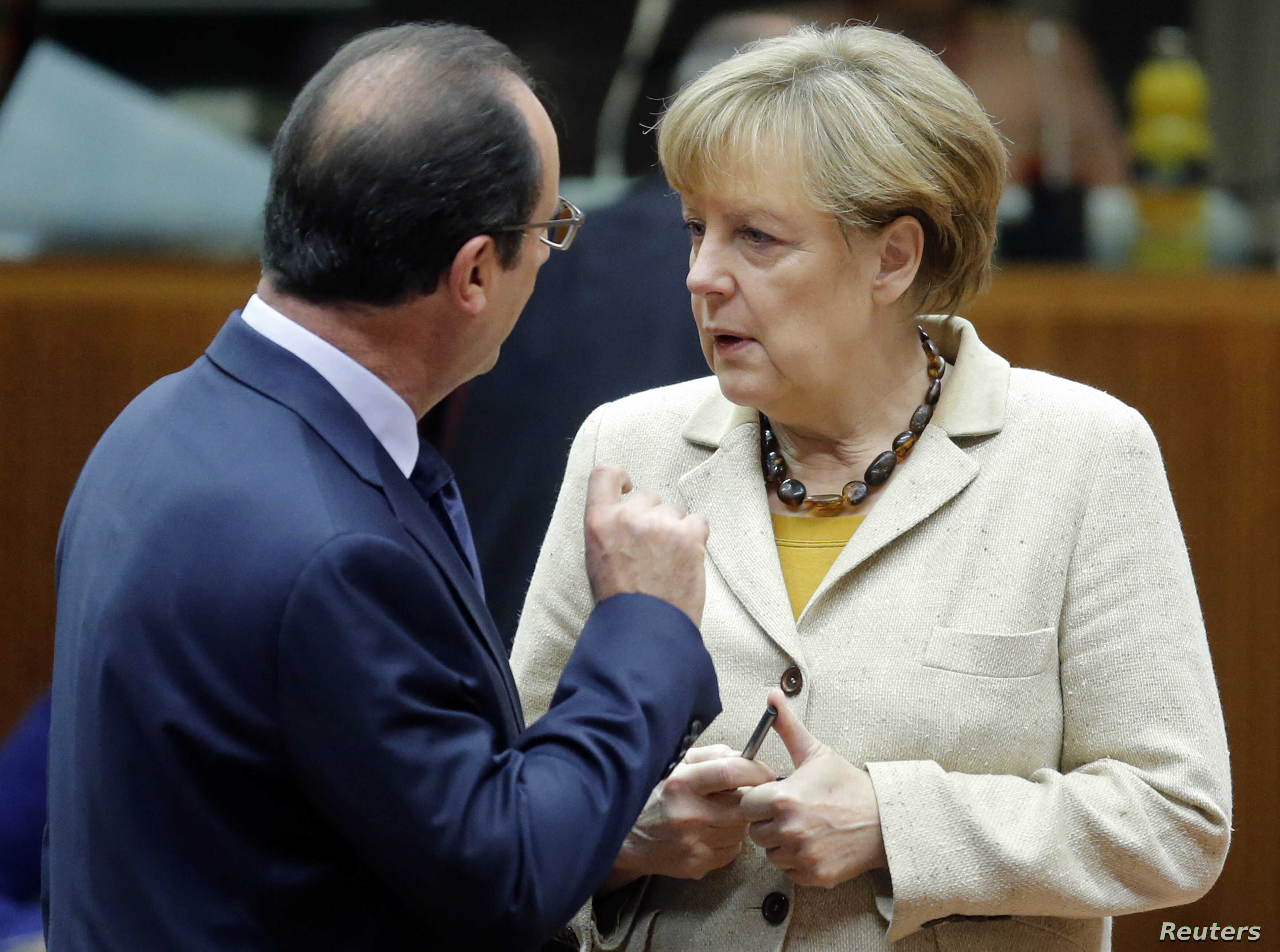 Germany's Chancellor Angela Merkel (R) and France's President Francois Hollande arrive for a working session during an EU summit in Brussels, Oct. 24, 2014.