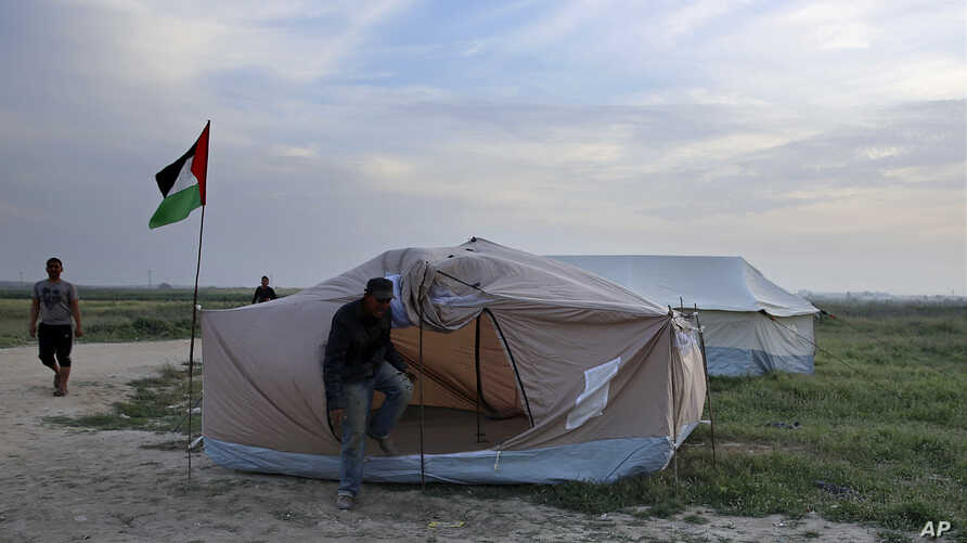 Palestinians set up tents in preparation for mass demonstrations along the Gaza Strip border with Israel, in eastern Gaza City, March 27, 2018. Gaza's embattled Hamas rulers are imploring hundreds of thousands of people to march along the border with