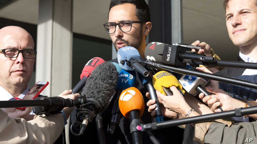 Spanish rapper Jose Miguel Arenas Beltran, also known as Valtonyc, center, speaks with the media with his two lawyers, Gonzalo Boye, left, and Simon Bekaert, right, as he leaves the courthouse in Ghent, Belgium, Sept. 17, 2018.