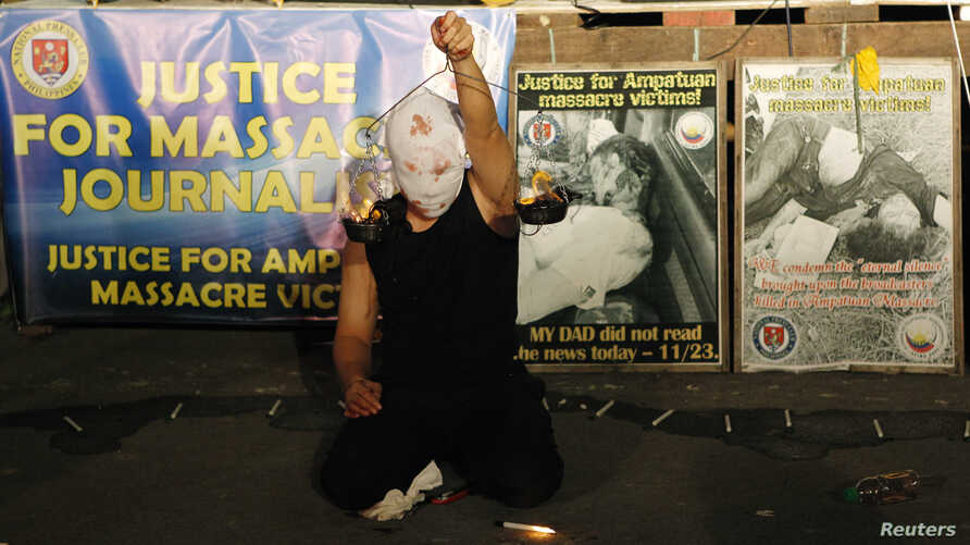 """A masked Filipino artist holds up a replica of a burning weighing scale signifying justice to commemorate the 2nd year anniversary of the """"Maguindanao Massacre"""" at the National Press Club compound in Manila November 23, 2011."""