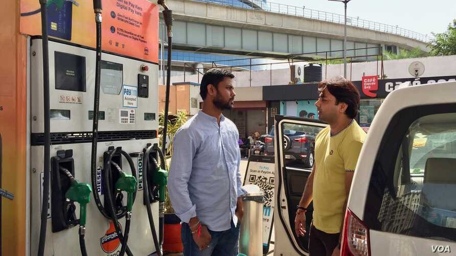 Rajesh Kumar, left, shares a ride to work with another employee, Dilip Swain, right, as higher petrol prices in India begin to be felt in people's pocketbooks.