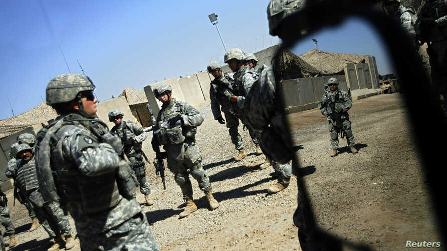 U.S. soldiers from the 2nd battalion, 32nd Field Artillery brigade listen to their superiors' orders before going on a patrol in Baghdad Aug. 14, 2007.
