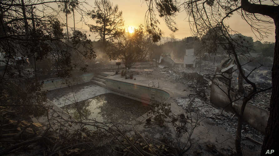 The sun rises behind a home leveled by the Holiday fire in Goleta, Calif., July 7, 2018. Evacuations were ordered as the fire edged into residential areas.