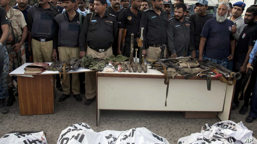 Police officers display confiscated ammunition and the dead bodies of terrorists who attacked the Jinnah International Airport Monday in Karachi, Pakistan, June 9, 2014.