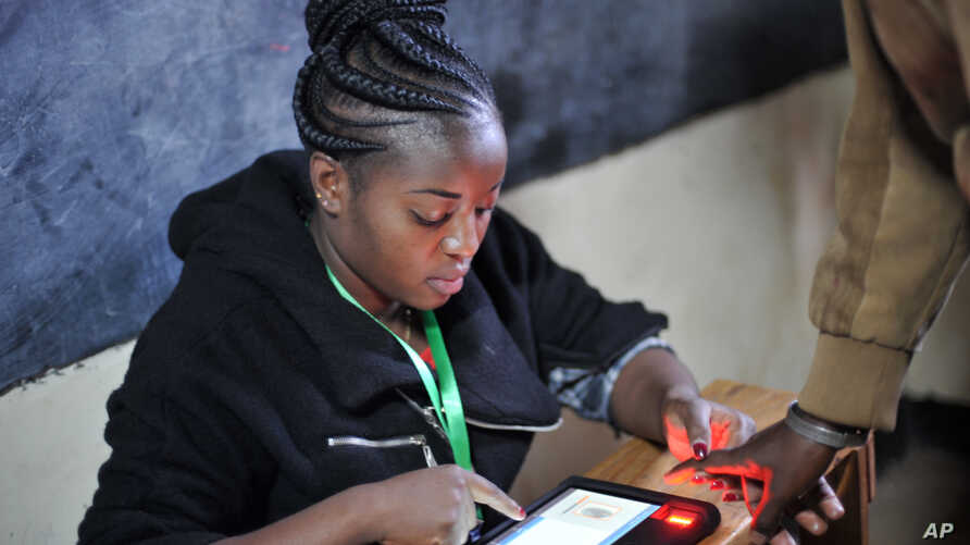 An offical from the electoral commmision registers voters through a fingerprint scan machine at the Panarae Primary School in Kajiado, Kenya, Aug. 8, 2017.