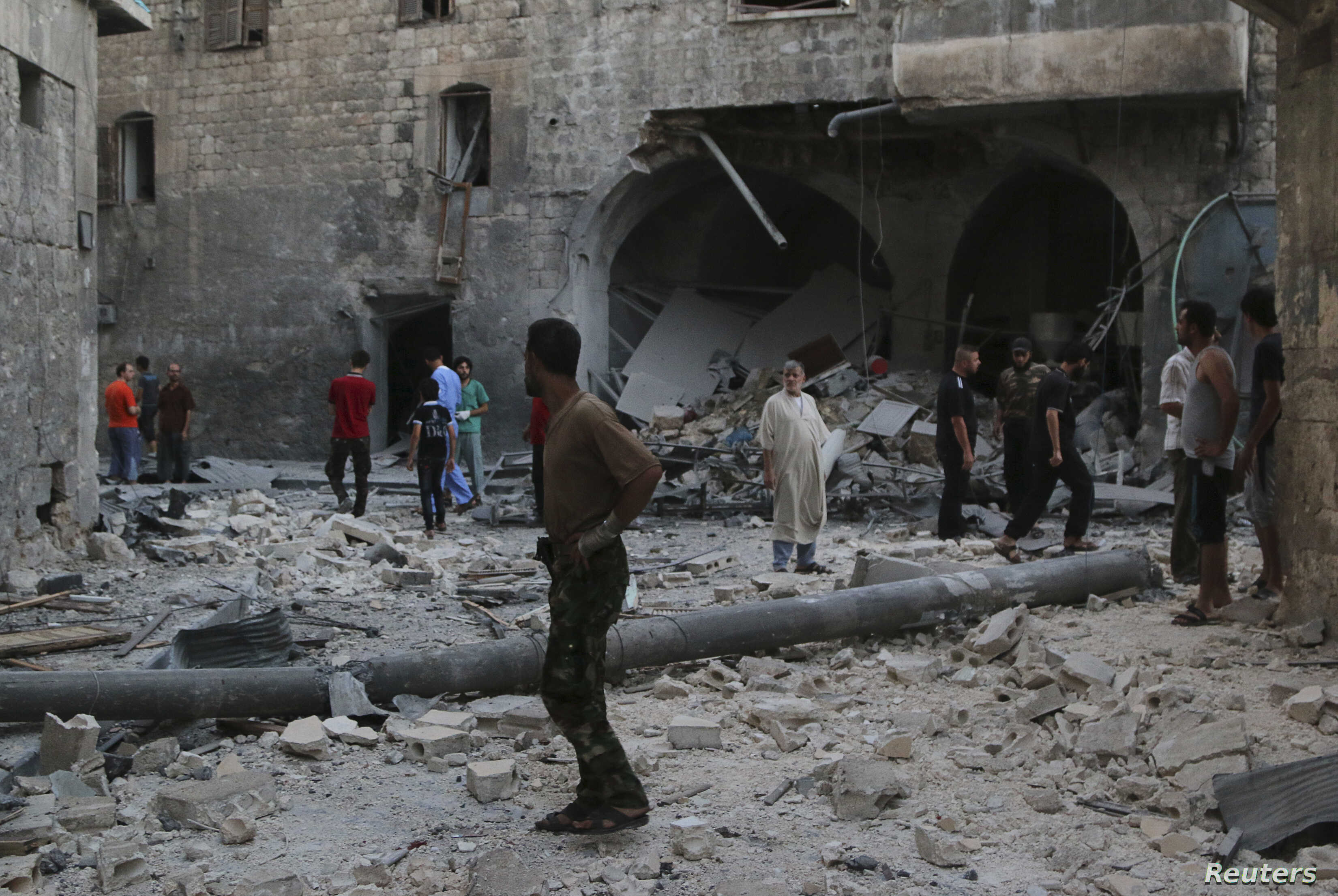 People inspect a site hit by what activists said was an airstrike by forces loyal to Syria's President Bashar al-Assad, in Qadi Askar district in Aleppo, Syria, July 21, 2014.