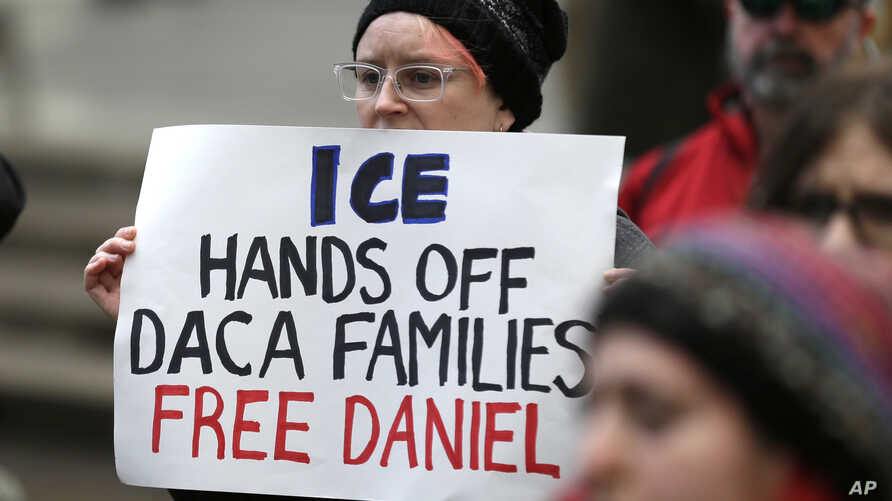 FILE - In Feb. 17, 2017, photo, a protester stands in Seattle. A federal judge upheld a decision not to release Daniel Ramirez Medina, a Mexican arrested near Seattle, despite his participation in the DACA program.