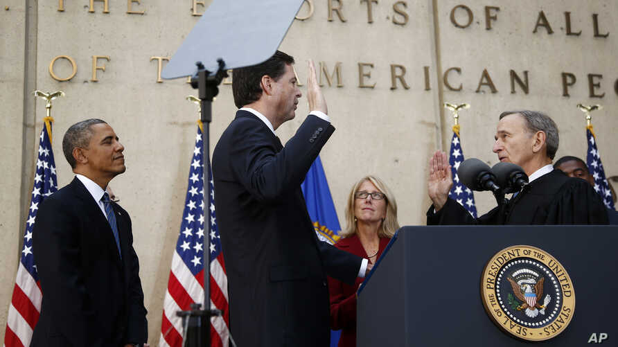 President Barack Obama watches as FBI Director James Comey takes an oath as FBI director from Judge John Walker, right, as Comey's wife Patrice Failor watches at center, during Comey's installation ceremony at FBI Headquarters in Washington, Oct. 28,