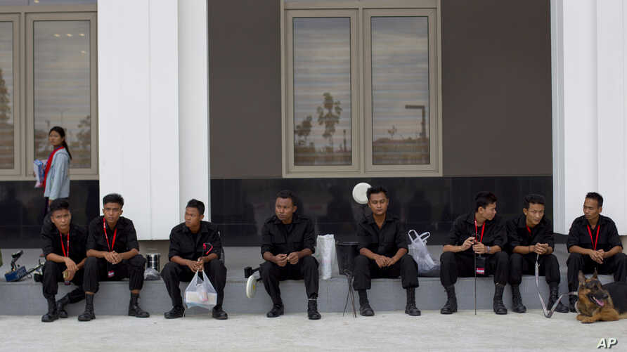 Sniffer dogs and members of Burma's bomb squad rest after checking Myanmar International Convention Center, the venue for the 24th ASEAN Summit for explosives in Naypyitaw, Burma, May 9 2014.