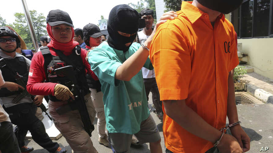 Police escort a suspect involved the making of toxic bootleg alcohol after a press conference in Jakarta, Indonesia, Wednesday, April 11, 2018.