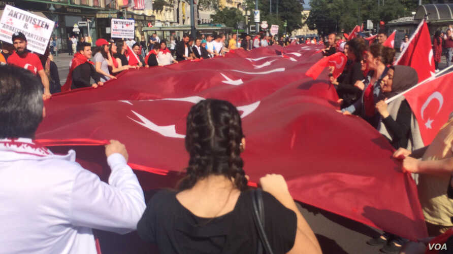 Demonstrators carry a large Turkish flag, saying they are not just protesting the attack in Istanbul, but the increasing tendency to conflate Islam and terrorism, in Vienna, Austria, July 3, 2016. (H. Murdock/VOA)