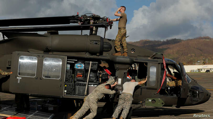 Soldiers with the U.S. Army's 1st Armored Division, Combat Aviation Brigade, work to unload a UH-60 Blackhawk helicopter from a U.S. Air Force C-5 Galaxy to aid in recovery efforts following Hurricane Maria, Puerto Rico, Oct. 4, 2017.