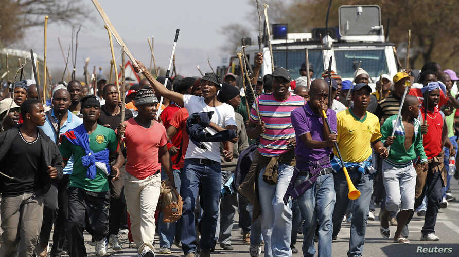 Mineworkers take part in a march outside the Anglo American mine in South Africa's North West Province, September 12, 2012.
