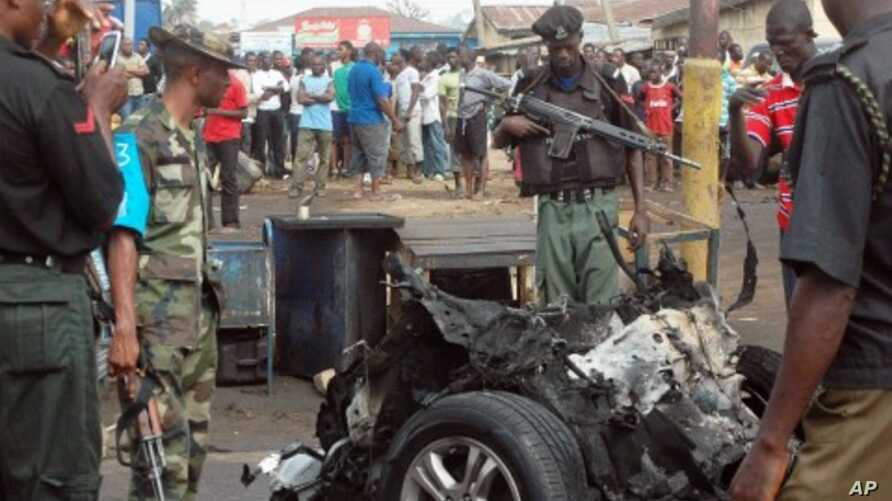 Security personnel inspect the mangled remains of bomb-laden car that exploded  along junction road near a church, Kaduna, Nigeria,  April 8, 2012.