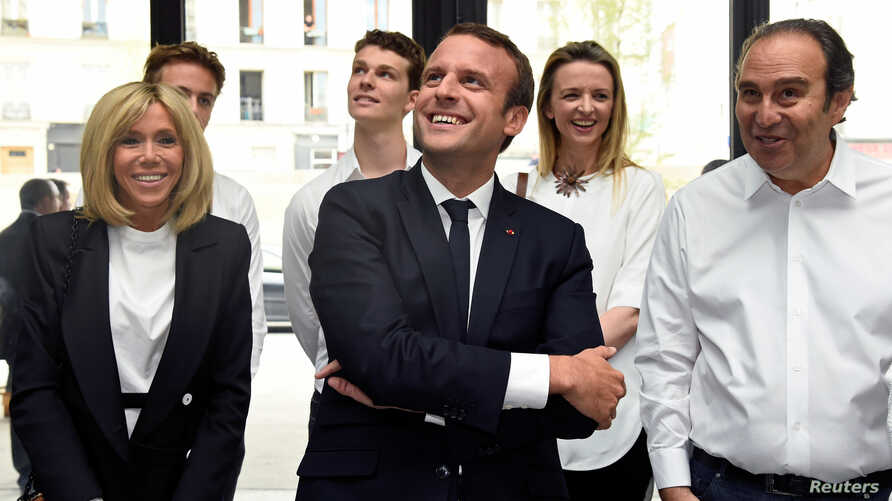 """France's President Emmanuel Macron and his wife Brigitte speak with French entrepreneur and businessman Xavier Niel, right, during the inauguration of start-ups incubator """"Station F"""", in Paris, France, June 29, 2017."""
