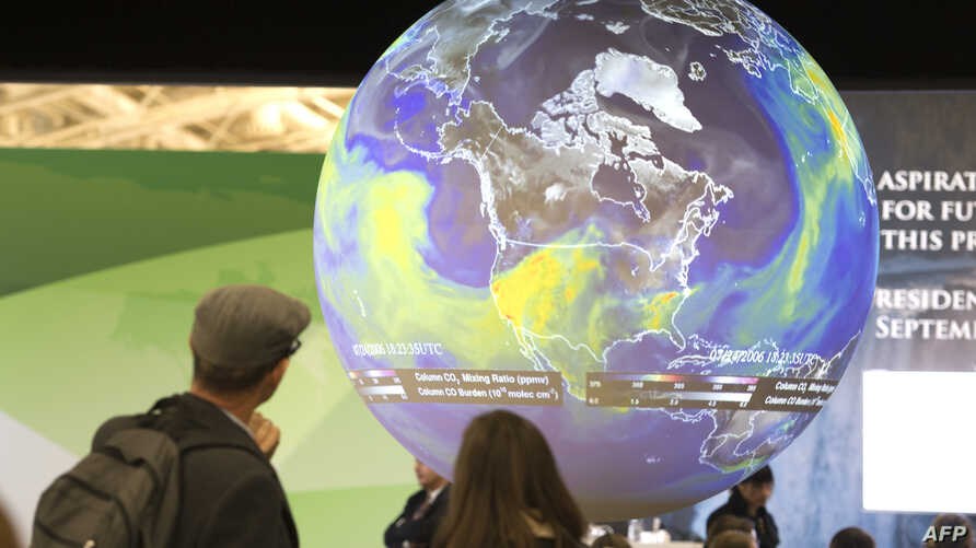 People watch the Earth globe at the COP21, the United Nations conference on climate change in Le Bourget, Dec. 10, 2015.
