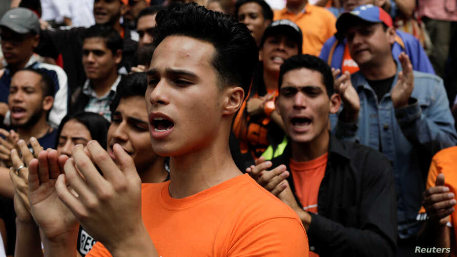 Opposition supporters shout during a gathering in front of the United Nations offices in Caracas, Venezuela, March 12, 2018.