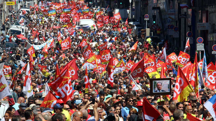 Workers hold flags and demonstrate during a day of strikes and protests, in Marseille, southern France, June 14, 2016.