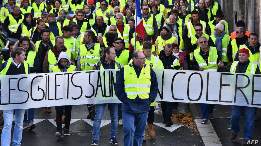 """Yellow Vests (Gilets jaunes) march behind a banner reading """"Yellow vests are angry"""" as they protest high fuel prices in Rochefort, southwestern France, Nov. 24, 2018, part of a movement which has spread into a widespread protest against stagnant spen"""