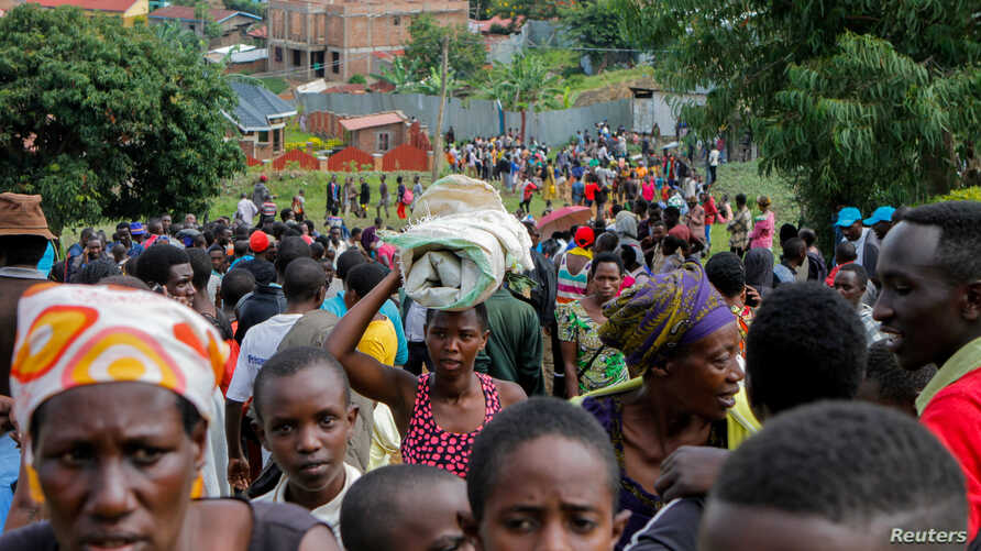 Refugees from the Democratic Republic of Congo carry their belongings as they walk near the United Nations High Commissioner for Refugees (UNHCR) offices in Kiziba refugee camp in Karongi District, Rwanda, Feb. 21, 2018.