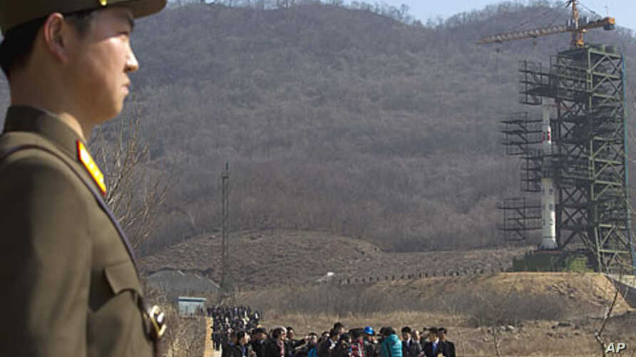 A crowd of media gather around a North Korean official in front of North Korea's Unha-3 rocket, slated for liftoff between April 12-16, at Sohae Satellite Station in Tongchang-ri, North Korea, April 8, 2012.