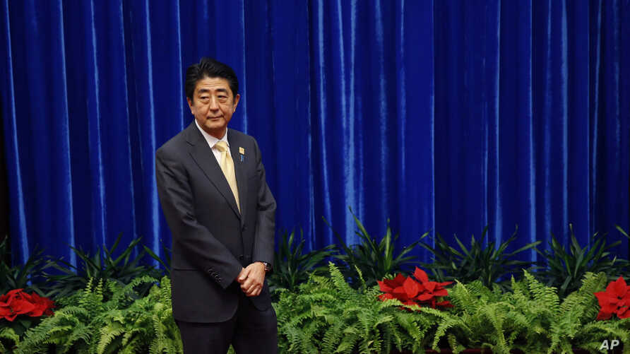 FILE - Japan's Prime Minister Shinzo Abe wait to meet China's President Xi Jinping, during their meeting at the Great Hall of the People, on the sidelines of the Asia Pacific Economic Cooperation (APEC) meetings, in Beijing, Monday, Nov. 10, 2014.