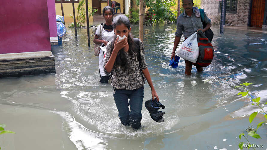 Residents carry their belongings as they evacuate their house after flooding caused by Cyclone Ockhi in the coastal village of Chellanam in the southern state of Kerala, India, Dec. 2, 2017.