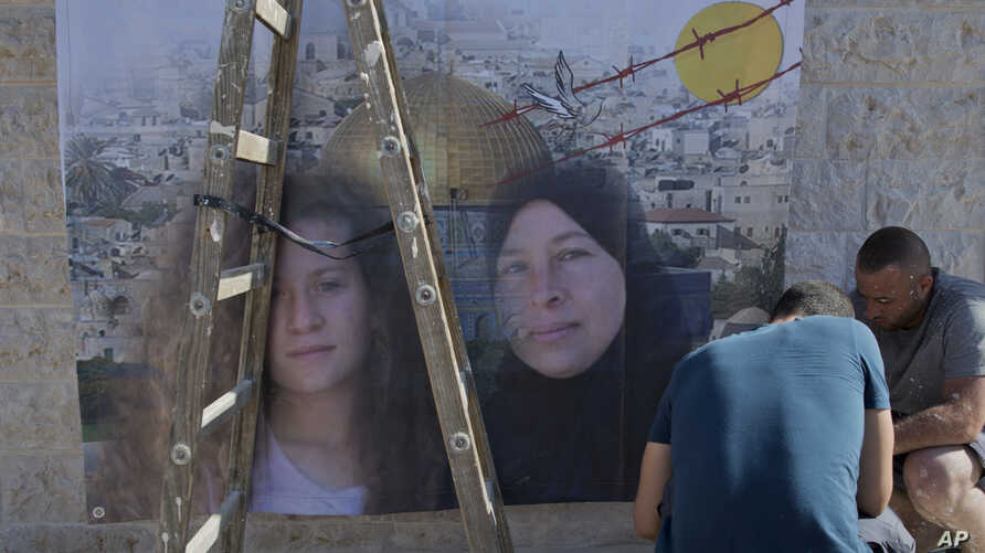 Palestinians hang a poster showing Nariman Tamimi, right, and her daughter, Ahed, during preparations for their upcoming release from an Israeli prison after serving an eight-month sentence, at the family house in the West Bank village of Nabi Saleh,