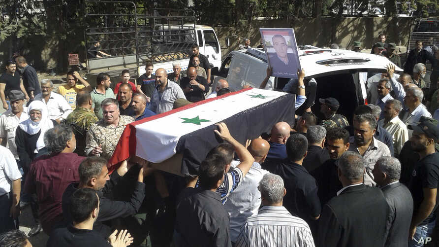 In this photo released by the Syrian official news agency SANA, mourners carry a coffin of one of the more than 200 people who were killed a day earlier by suicide bombings launched by the Islamic State's fighters on the eastern and northern countrys