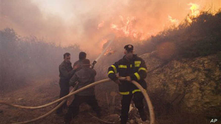 Firefighters try to extinguish the flames in Tirat Hacarmel, northern Israel, 03 Dec 2010