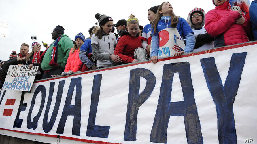 FILE -  Fans stand behind a large sign for equal pay for the women's soccer team during an international friendly soccer match between the United States and Colombia in East Hartford, Conn., April 6, 2016.