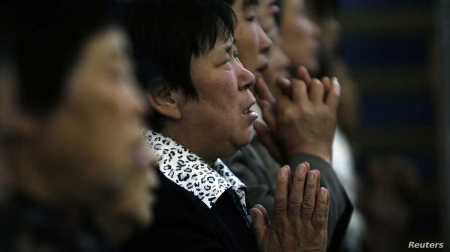 FILE - A woman prays with other villagers during a mass in the morning at the Liuhe Catholic Church in Liuhe village on the outskirts of Qingxu county, northern China's Shanxi province, Sept. 11, 2011.