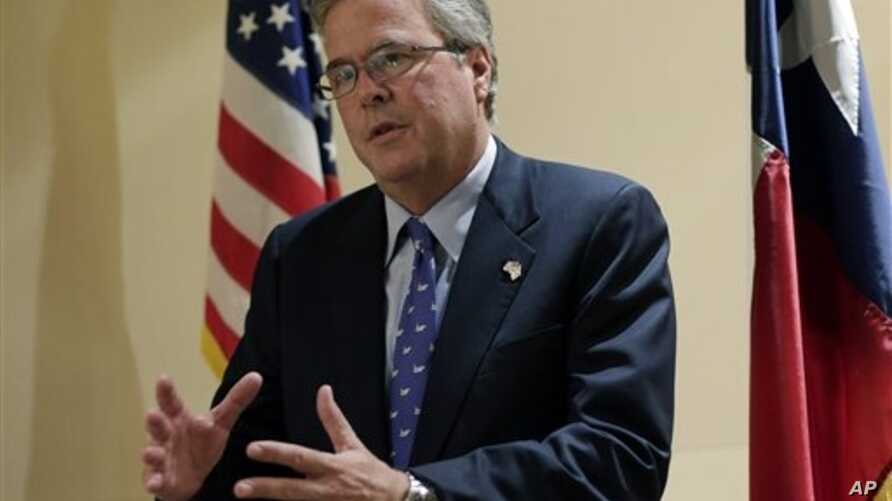 Former Florida Governor Jeb Bush talks with the media following his address on education to the Texas Business Leadership Council in Austin, Texas. Bush writes in a new book that the nation needs to completely overhaul its immigration policies but ca